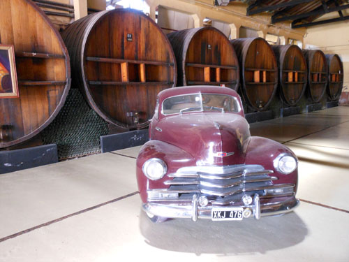 Argentina, Maipu, Baudron winery - huge out of use oak wine barrels and classic car